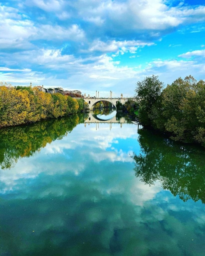 Ponte Milvio reflected in the water of the Tiber and edited in shades of teal and greens.