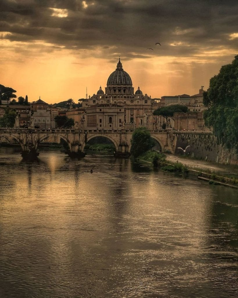 View of Ponte Umberto I crossing the Tiber in Rome with St. Peter's Basilica in the background, edited in shades of gold.
