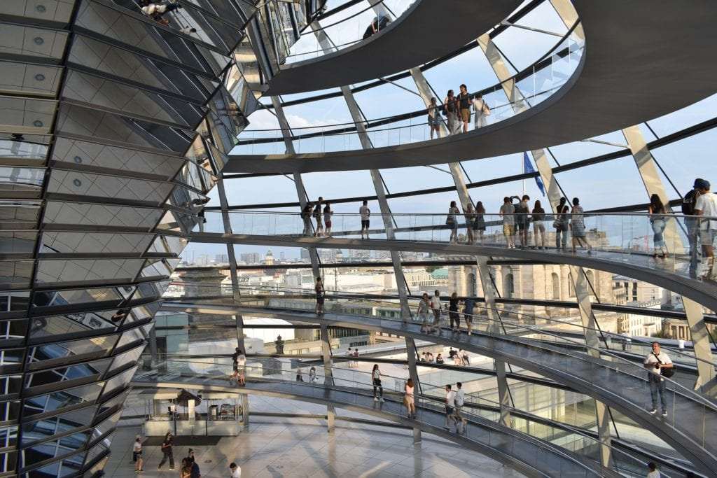 Interior of the Reichstag building in Berlin, Germany with people walking around its perimeter.
