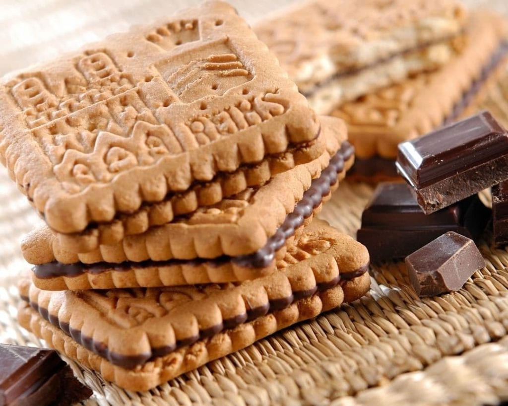 Close-up photo of Reims Biscuits with little broken pieces of chocolate alongside.