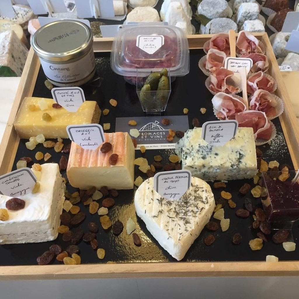 Display of many different cheeses with labels, dried fruits and nuts, jambon, cornichons, and other regional specialties in Reims, France.