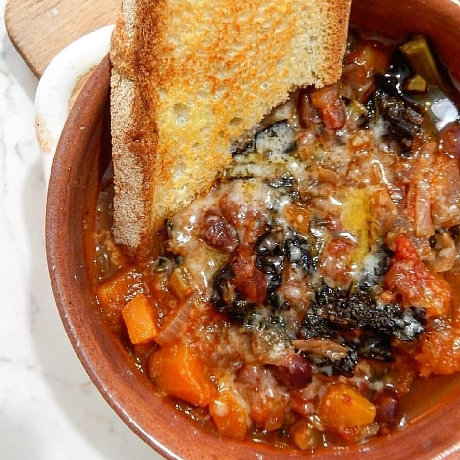 Hearty bread-based stew with melted grated parmesan on the top.