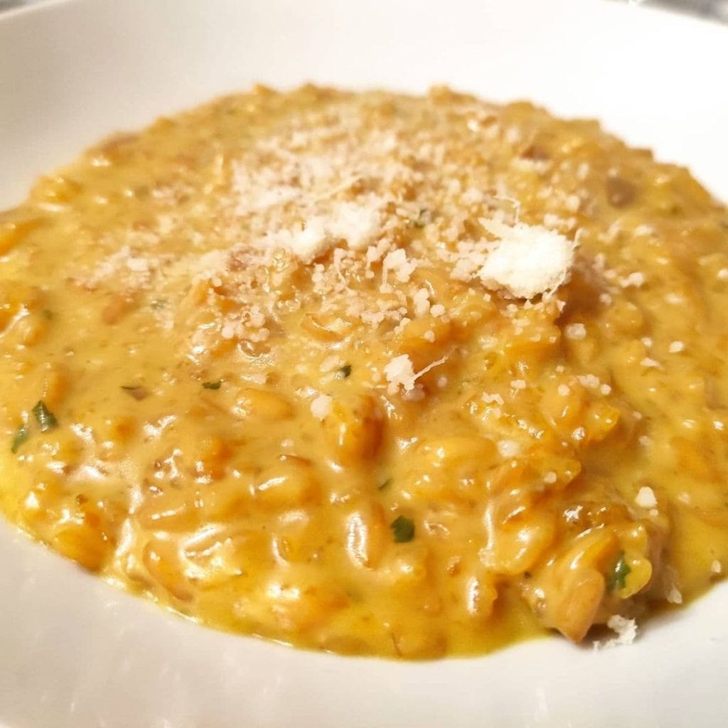 A heaping plate of creamy orange risotto topped with grated cheese.