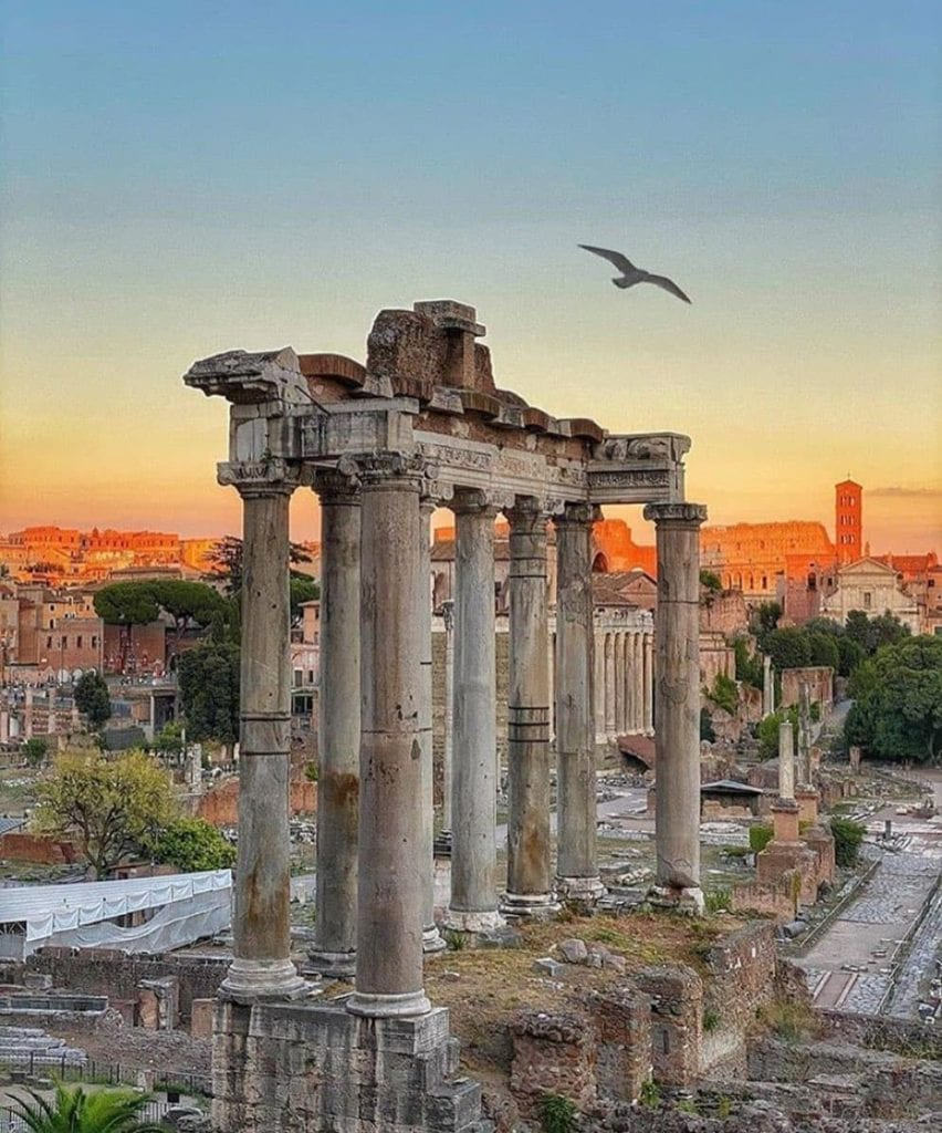 View of the Roman Forum during one of Rome's bright orange sunsets with birds flying overhead.