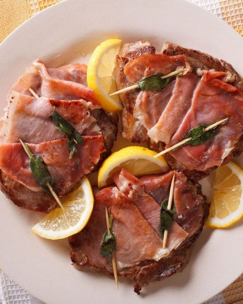 Sliced veal topped with prosciutto and sage leaves stuck through with toothpicks, surrounded by lemon wedges, a traditional Italian dish.