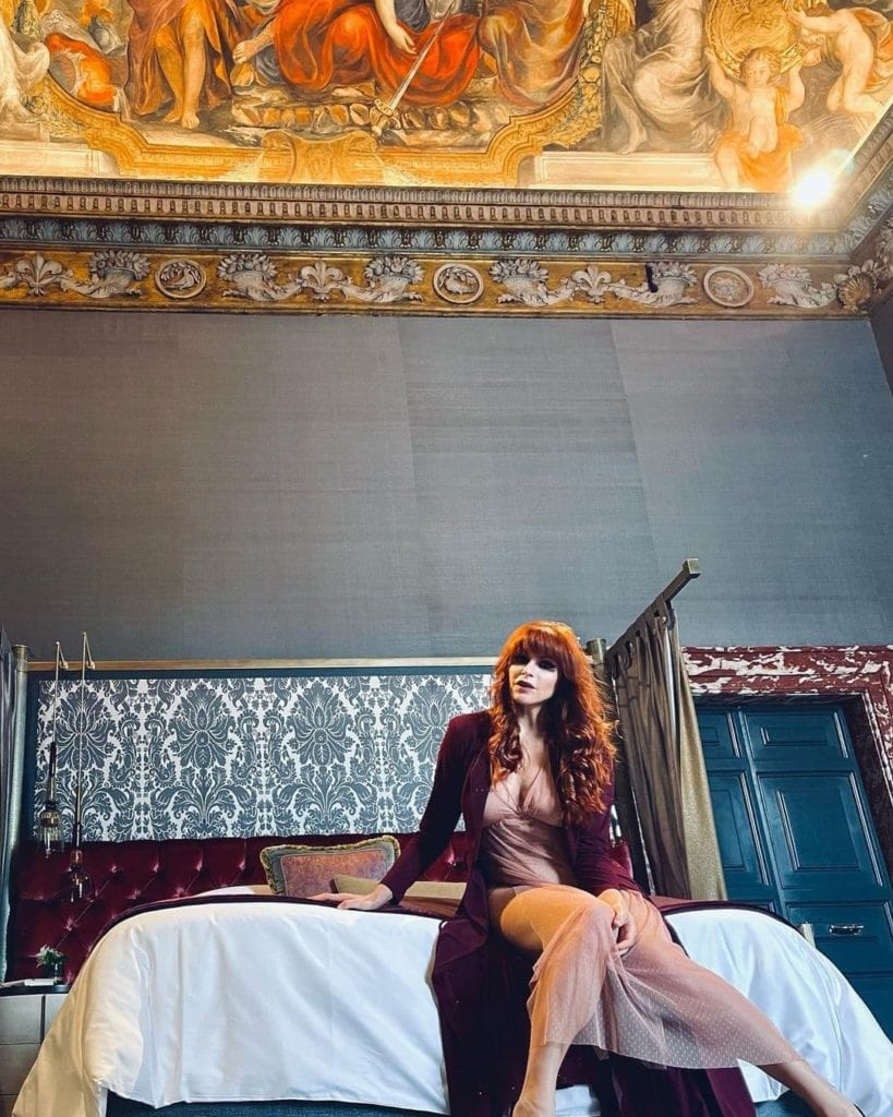 Woman sitting on the edge of a bed in a luxurious Roman hotel room.