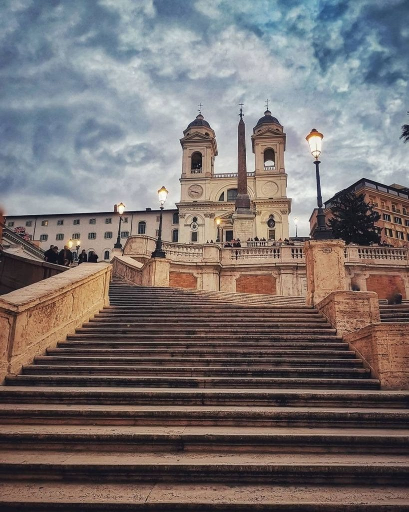 Looking up at the church from the bottom of the Spanish Steps during a cloudy evening with the street lamps turned on.