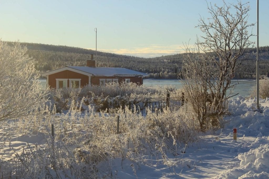 Wintery view of a small cottage on a train from Stockholm to Kiruna.