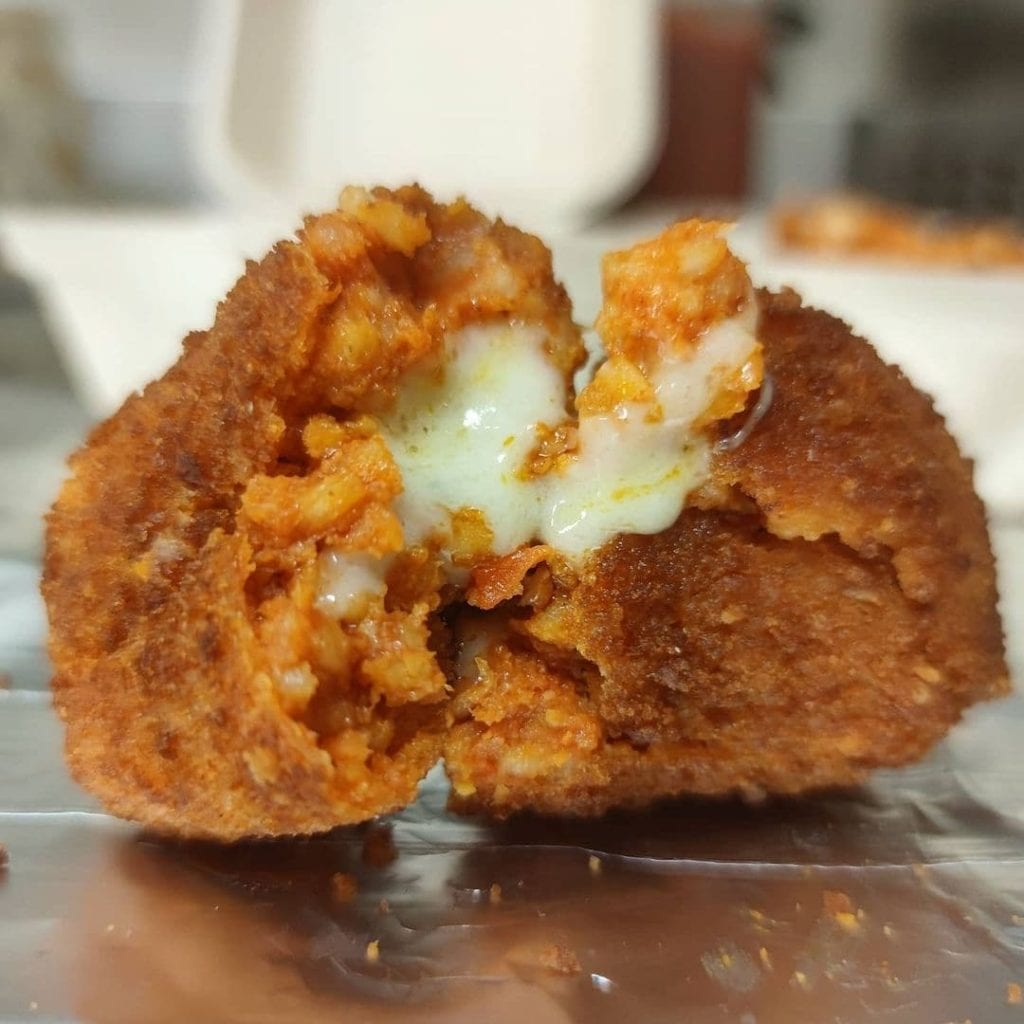 Close-up of an opened suppli, a traditional Roman street food.
