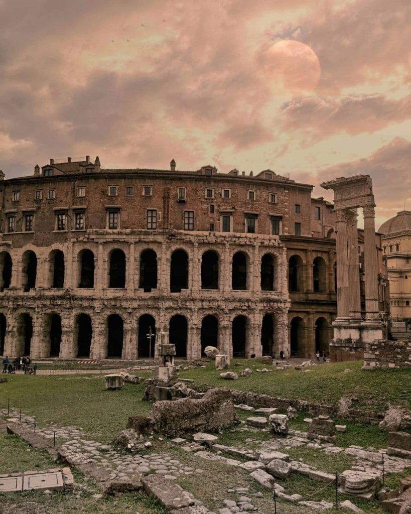 Teatro di Marcello with pink skies and the faint outline of a moon rising.