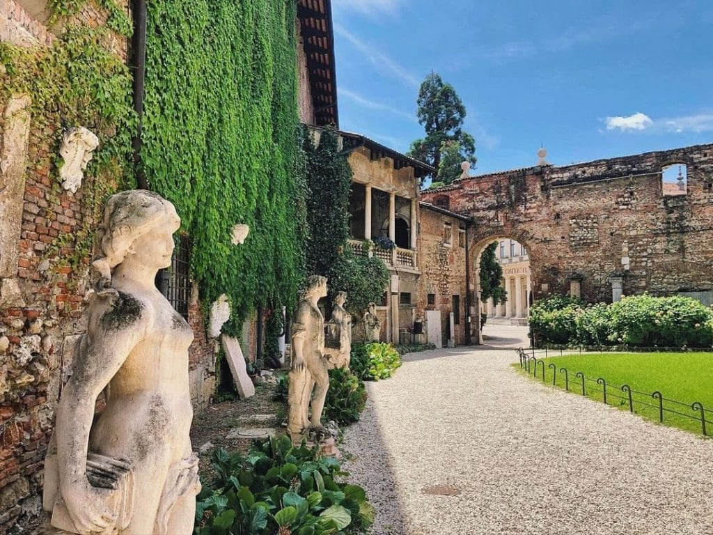 Ivy covered buildings and statues lining the perimeter of the garden outside Teatro Olimpico in Vicenza, one of the best things to do in the city.