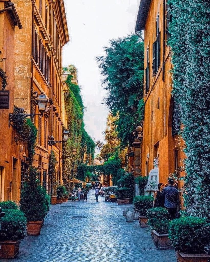 Orange hued buildings lining a street with many shrubs and cobblestones in Rome.
