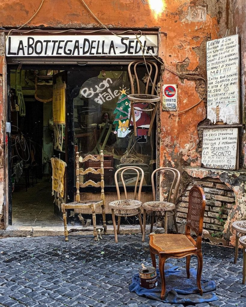 Dilapidated storefront with the text: La Bottega della Sedia, with many old chairs out front.