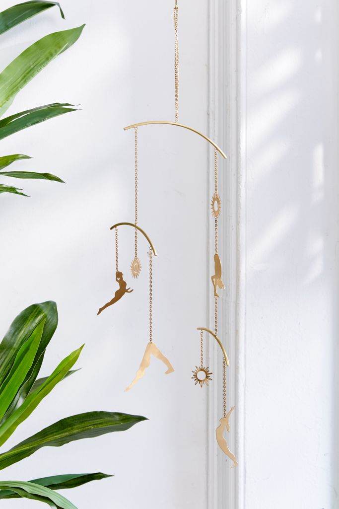 Gold hanging mobile with gold cut outs of different asanas in sun salutations.