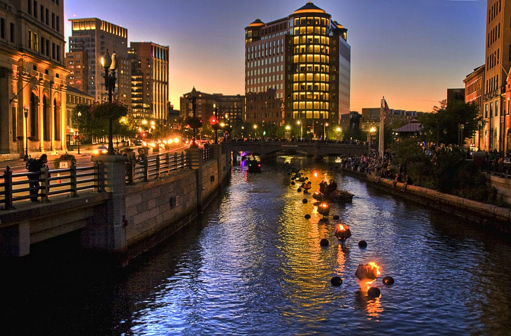 Providence Waterfire in Rhode Island with buildings iluminated during sunset.