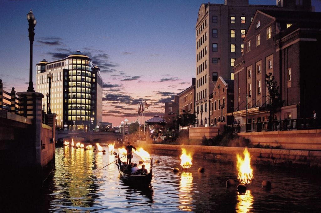 Gondola ride alongside fires at Providence Waterfire, one of the best day trips to take from Boston.