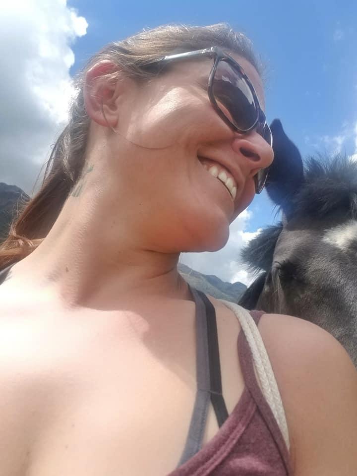 Woman taking selfie with wild horse in Cuenca, Ecuador