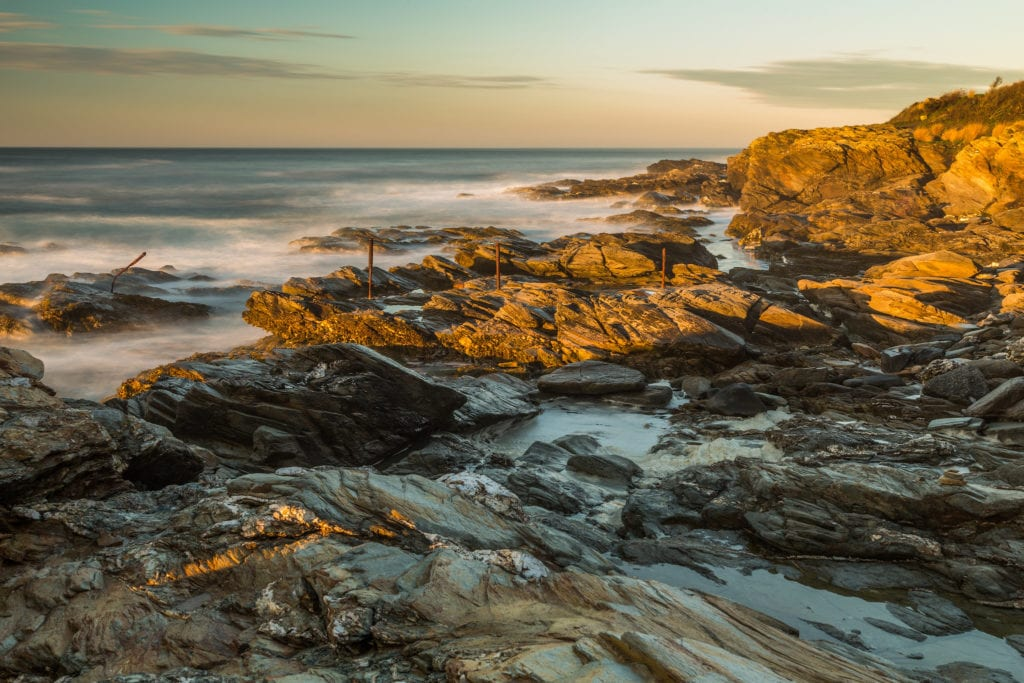 Beavertail State Park in low light in Rhode Island, waves crashing on the rocks.