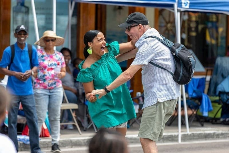 Two Bermudians dancing and laughing in the street during a Bermuda Day Festival