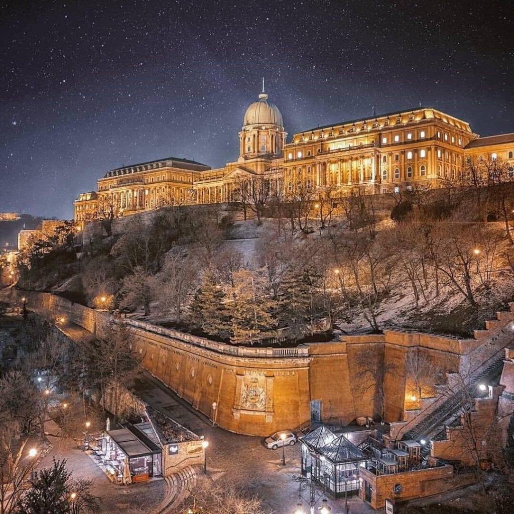 Buda Castle at night under a sky full of stars, illuminated in soft gold lights.