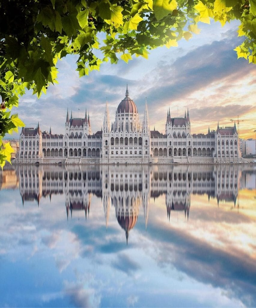 Budapest Parliament seen from behind green spring trees across the river.