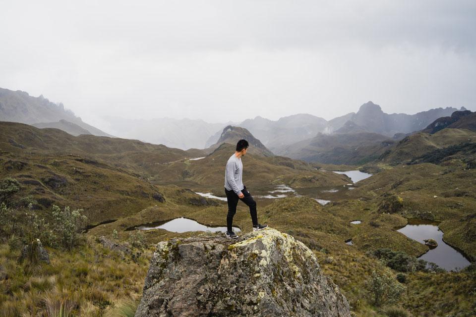 Man standing on rock in Cajas National Park in Ecuador, a great adventure in Ecuador.