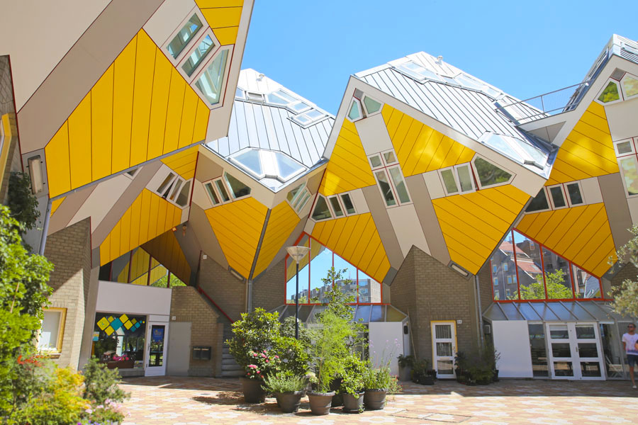 Yellow cube buildings in Rotterdam, Netherlands.  There are a number of potted plants in a courtyard in front of the buildings.  Rotterdam is one of the best cities to visit in the Netherlands.