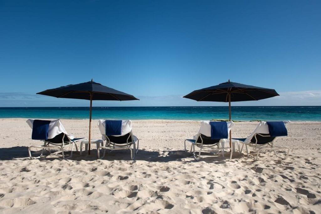 Chaise lounges with black umbrellas on Elbow Beach in Bermuda