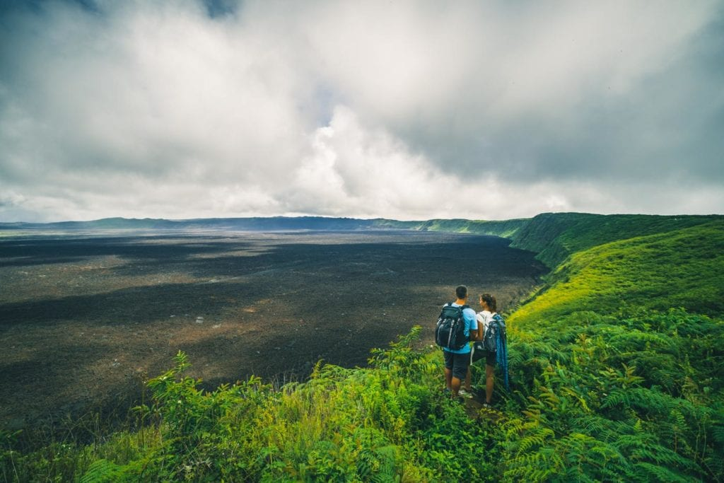 Hiking black sand beach at Cerro Negro on Isabela island in the Galapagos, a sure place for adventure in Ecuador.