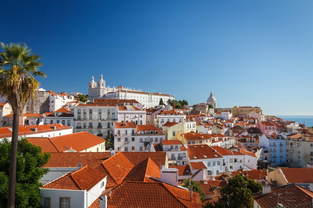 Red roofed buildings and palm trees scattered over the hills of Lisbon, Portugal, under a cloudless blue sky.