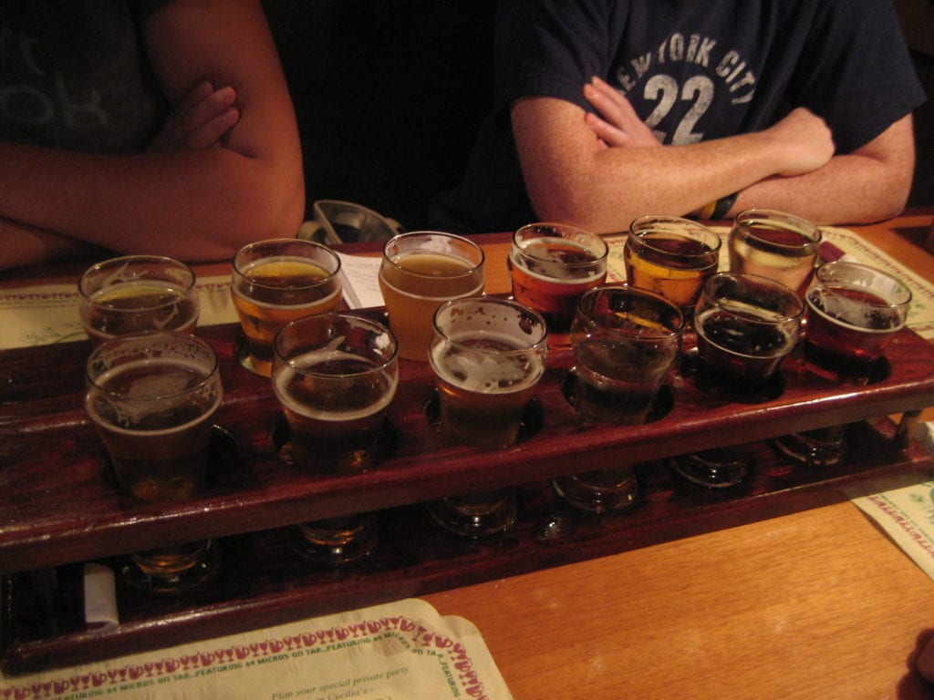 People sitting at a table with Mews beer flights in front of them.