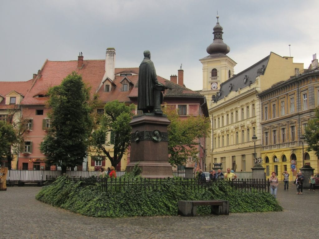 Piata in Sibiu, Romania with pale yellow and pink buildings, statue and green trees.