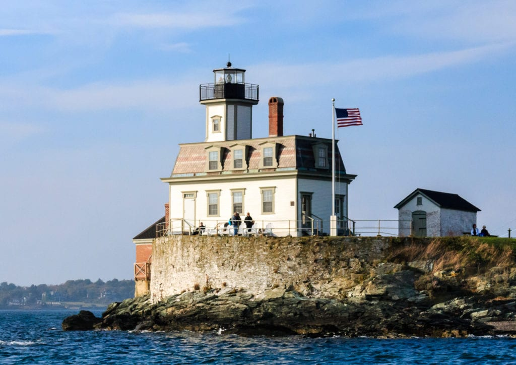 Haunted Rose Island Lighthouse in Rhode Island with American flag flying.
