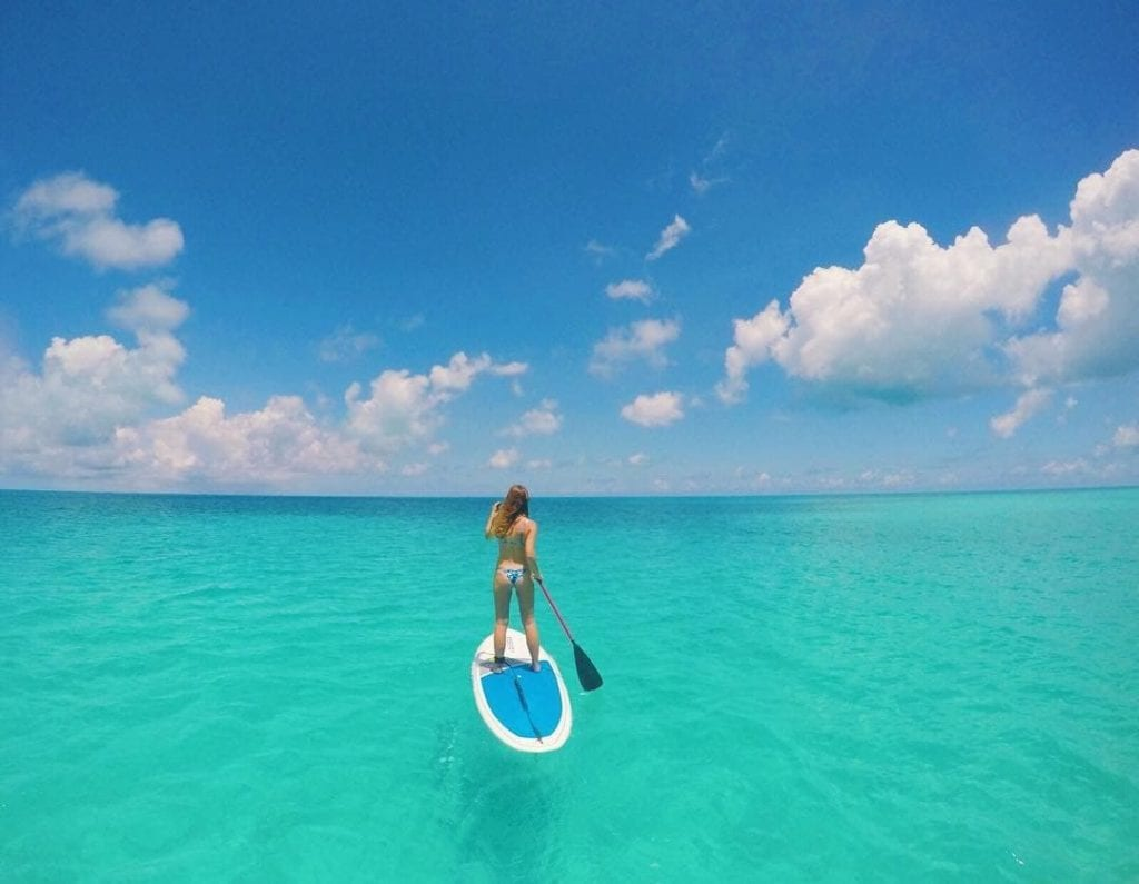 Woman stand up paddle boarding in Bermuda, paddling away from the camera