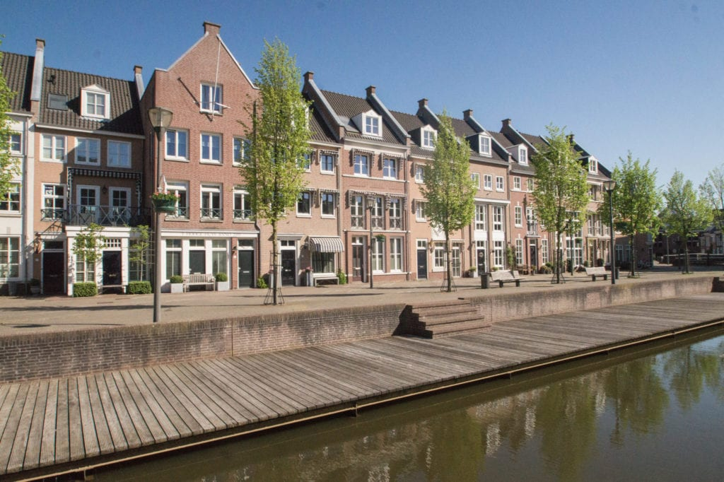 View of board walk and buildings lining a canal in Helmond, Netherlands.  There are young trees lining the canals and a slight reflection of them in the canal below.