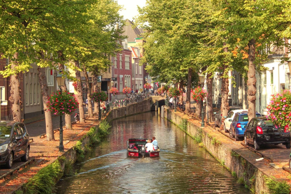 Looking down a canal in Amersfoort, Netherlands with a small boat going down the center of the river.  The canal is lined with spring trees and flowers.  One of the best cities to visit in the Netherlands.
