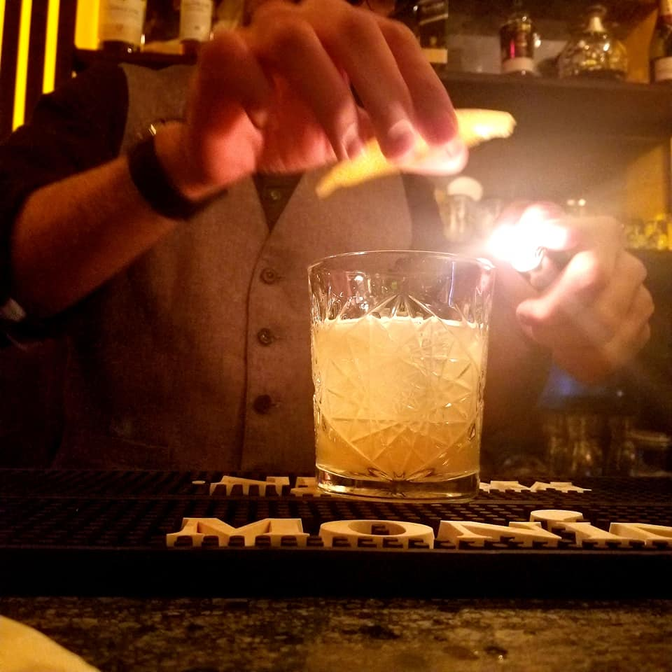 Man lighting citrus rind on fire before putting it into a cocktail at a bar in Budapest.