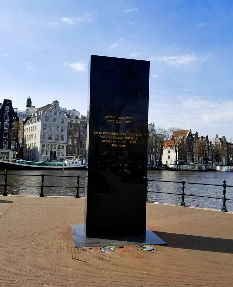 Photo of the Amstel monument with canals in the background.