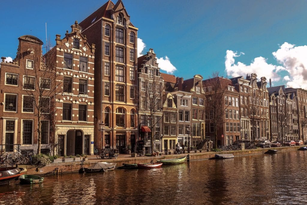 View of a canal with house boats and traditional Dutch buildings along the side of the canal in Amsterdam, Netherlands.