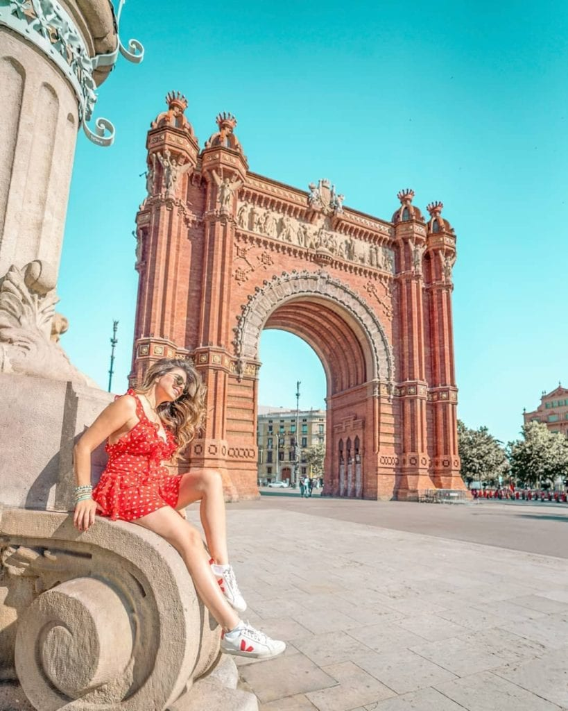 Woman in red polka dot dress and white sneakers posing in front of the Arc of Triumph in Barcelona, one of the most beautiful places in Barcelona.