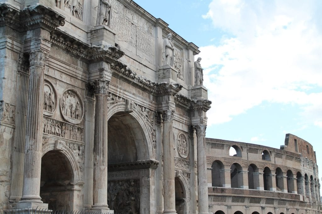 Arch of Constantine with the Colosseum in the background, both some of the most beautiful and Instagrammable places in Rome.
