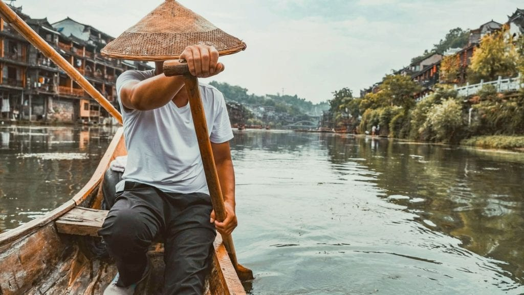 Man in straw hat paddling a boat down a river in Asia, virtual tours of Asia.