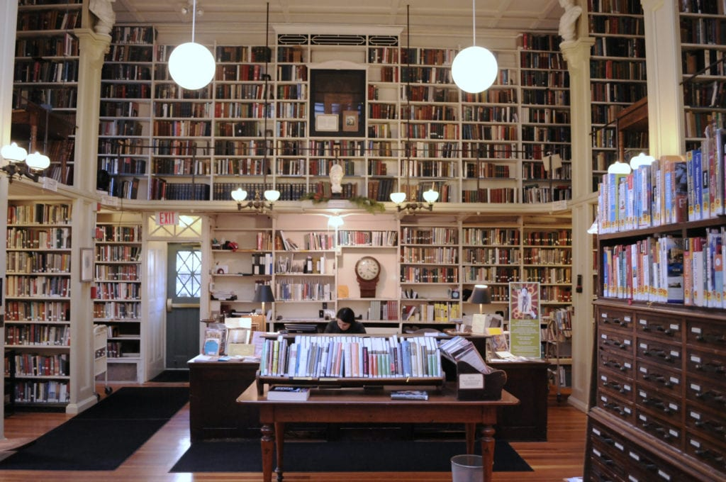 Providence Athenaeum, filled floor to ceiling with books and hanging globe lights.