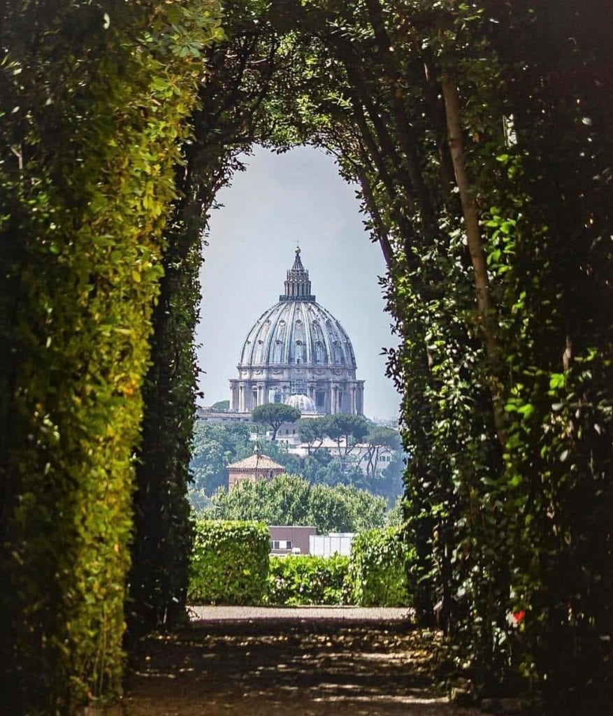 View through shrubs at the Aventine Keyhole with St. Peter's Basilica shown through the bushes.  The Aventine Keyhole is one of the most Instagrammable places in Rome.
