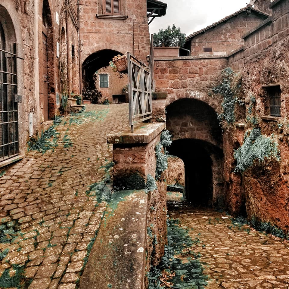 Winding paths and alleys of Barbarano Romano, one heading up and one heading down into the forest.