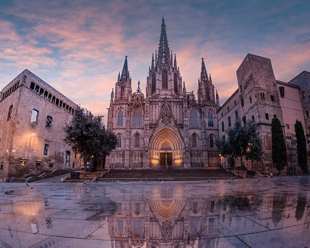 Barcelona Cathedral at twilight, reflecting in puddles below, one of the most beautiful places in Barcelona.