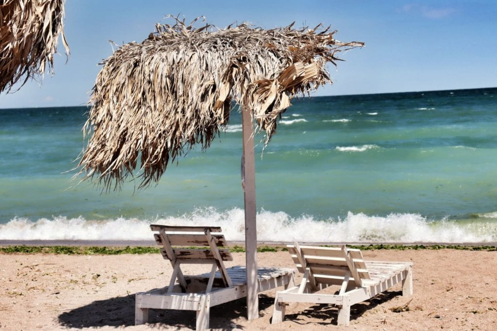 2 empty beach chairs in Vama Veche, Romania on the Black Sea coast in Romania.  VV is a hippie haven, one of the most underrated European beach destinations.