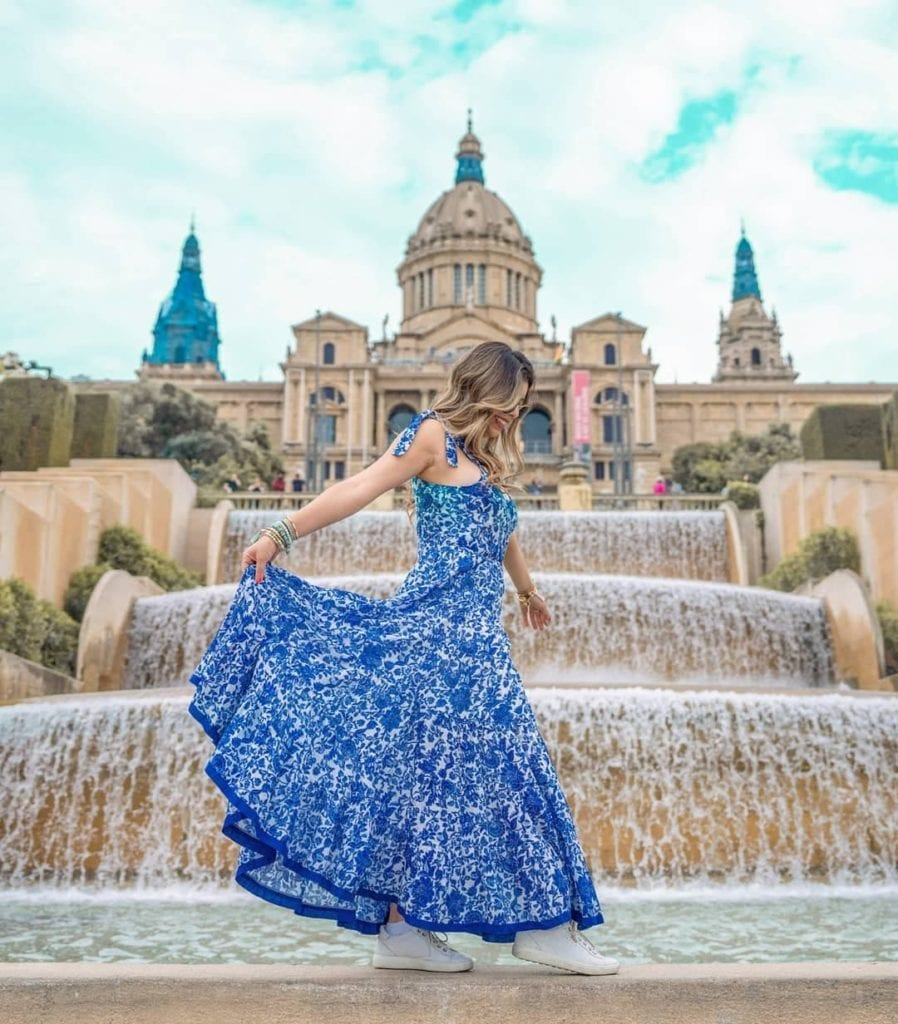 Woman in blue dress standing in the fountain at the National Art Museum of Catalunya, one of the most beautiful places in Barcelona.