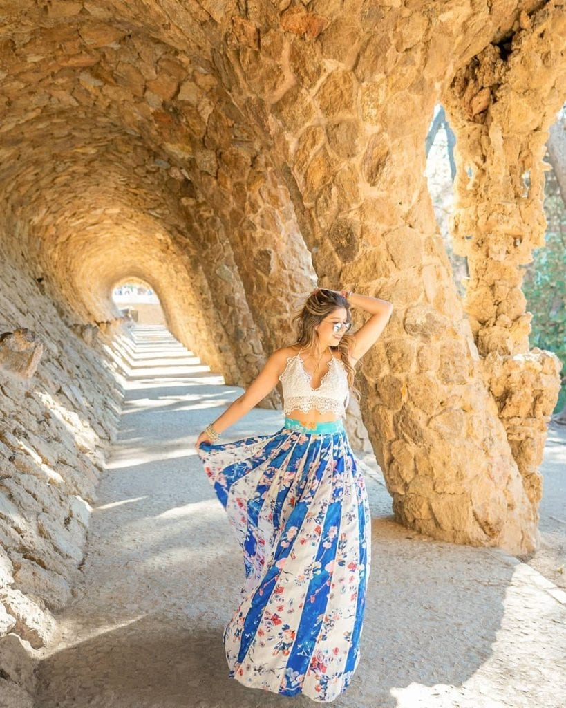 Woman in long blue skirt posing underneath the earthy columns at Parc Guell, one of the most beautiful places in Barcelona.