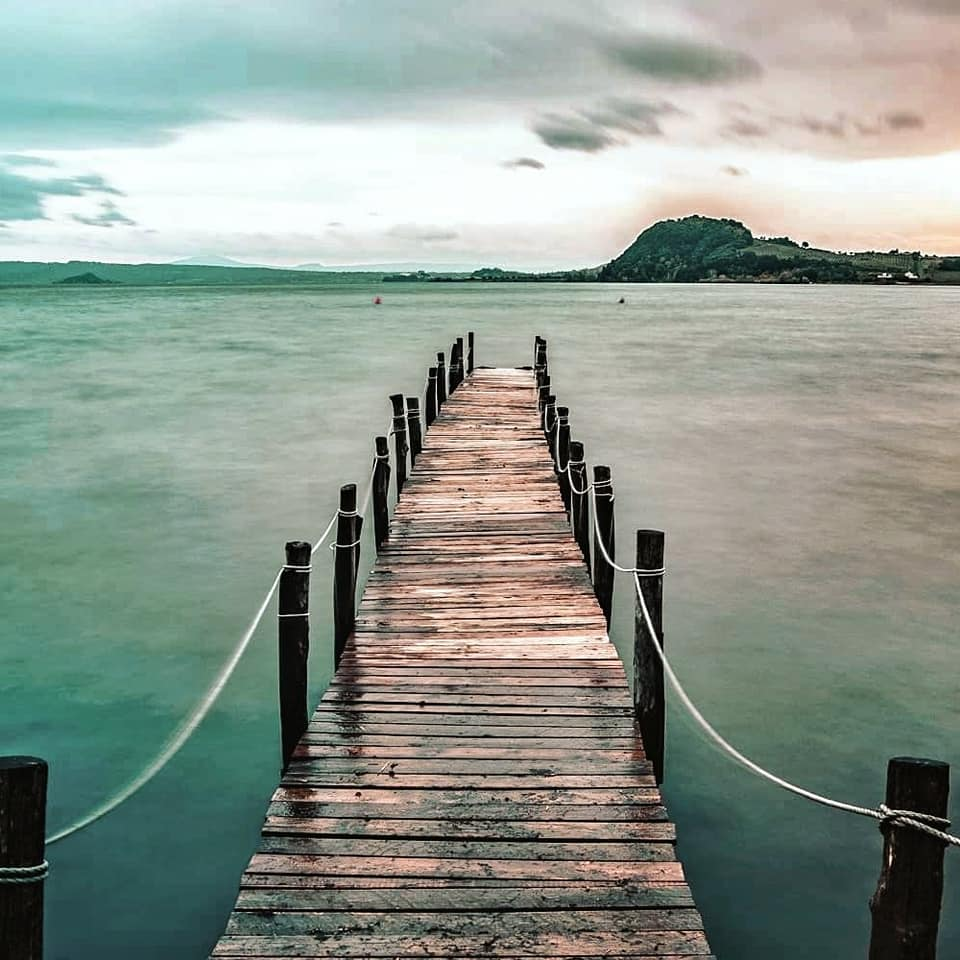 old wooden dock jutting out into the water on Lake Bolsena in Tuscia.